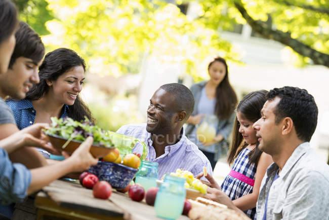 Amis assis à la table extérieure dans le jardin avec des fruits et légumes . — Photo de stock