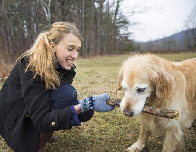 Jeune femme tenant bâton et jouer avec chien golden retriever. — Photo de stock