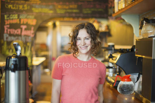 Young woman standing by coffee machine in cafe. — Stock Photo