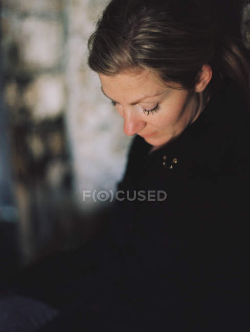 Woman wearing black coat looking down in pensive mood. — Stock Photo
