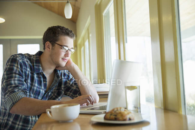 Young man sitting at cafe table and using laptop. — Stock Photo