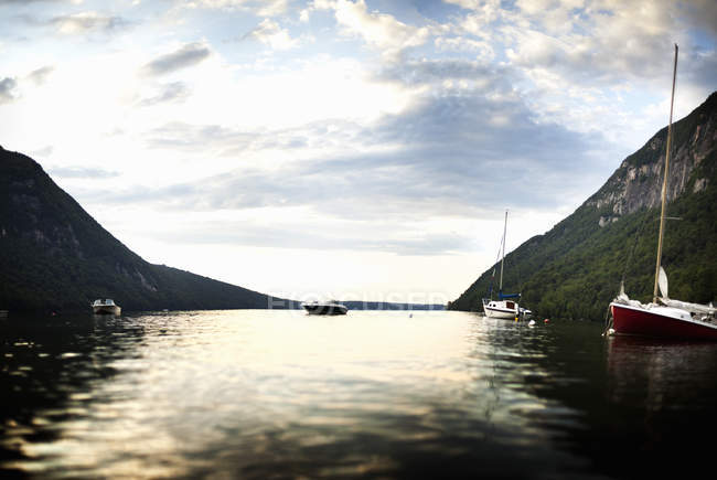 Boats, yacht and motorboat moored on calm lake in mountains. — Stock Photo