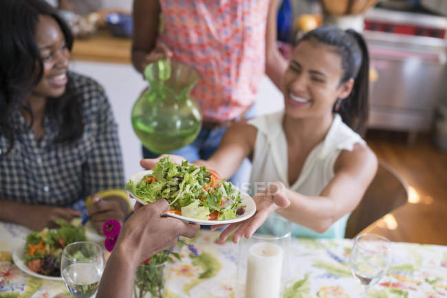 Group of women sharing salad while dinner in country kitchen interior. — Stock Photo