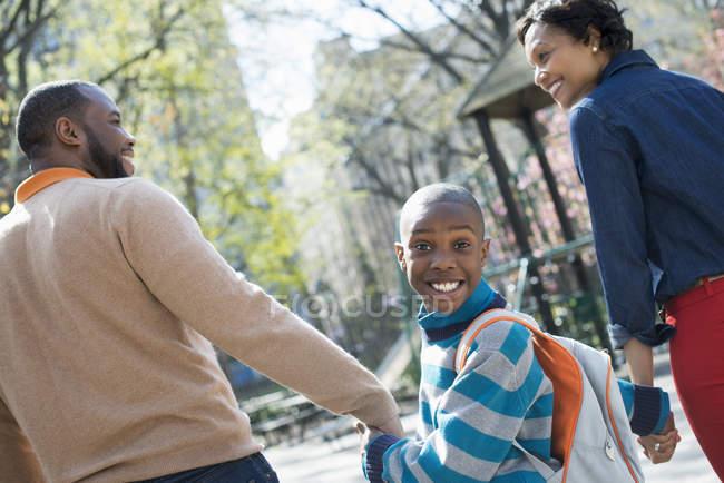 Хлопчик дивлячись через плече під час ходьби рука об руку з батьками на вулиці. — стокове фото