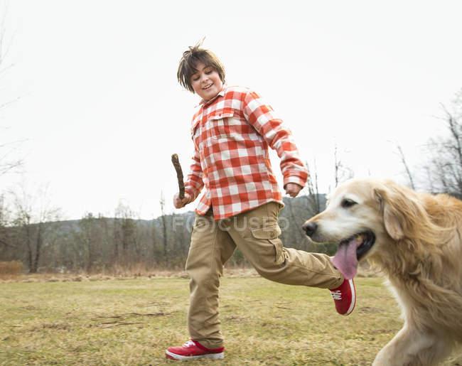 Adolescent, retenir le bâton et en cours d'exécution avec chien golden retriever. — Photo de stock