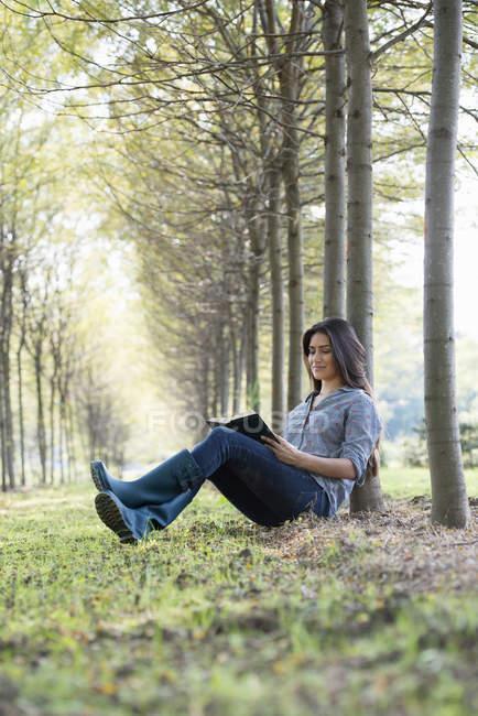 Mulher sentada e lendo o livro sob as árvores na floresta. — Fotografia de Stock