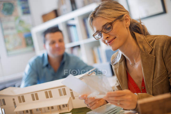 Two architects working on construction project using scale model of building. — Stock Photo
