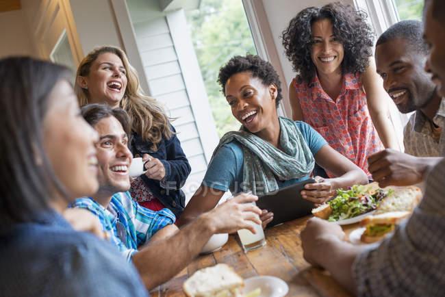 Groupe de personnes en train de déjeuner et à l'aide de tablette numérique à la réunion au café. — Photo de stock