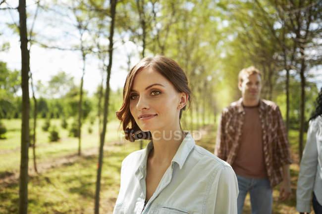 Junge Frauen und Männer gehen im Sommer auf Feldweg. — Stockfoto