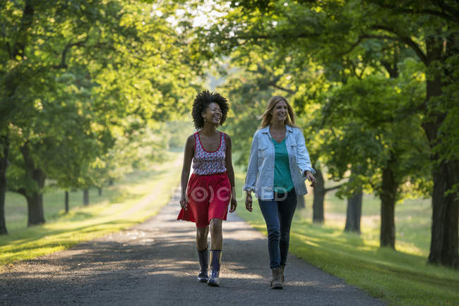 Two women walking down path in country park. — Stock Photo