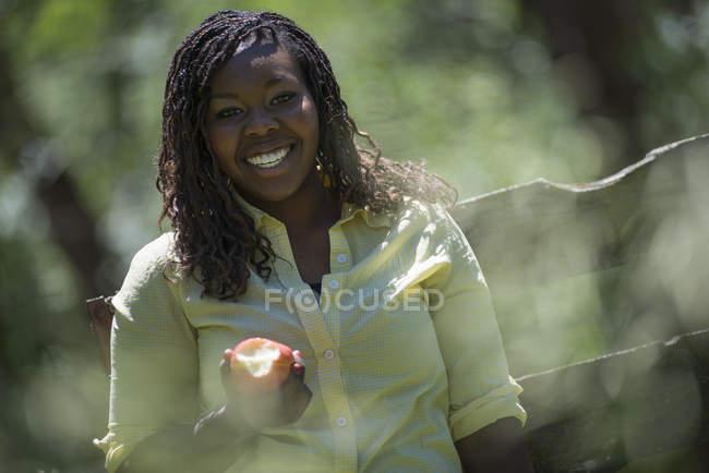Sorridente giovane donna che tiene mezza mela mangiata all'aperto . — Foto stock