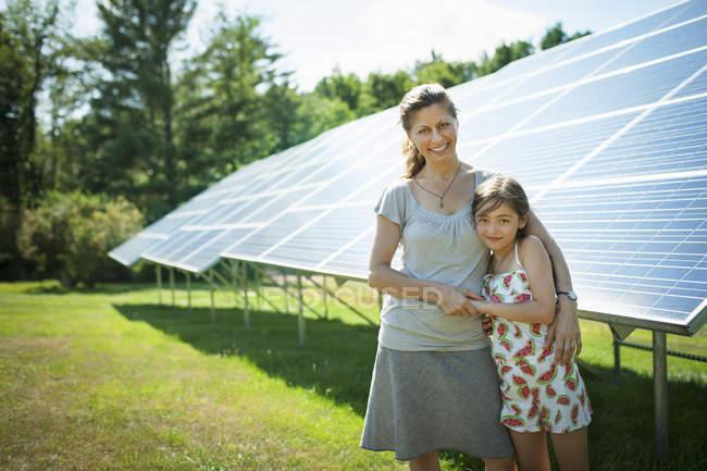 Ragazza pre-adolescente con madre in posa accanto ai pannelli solari in fattoria . — Foto stock