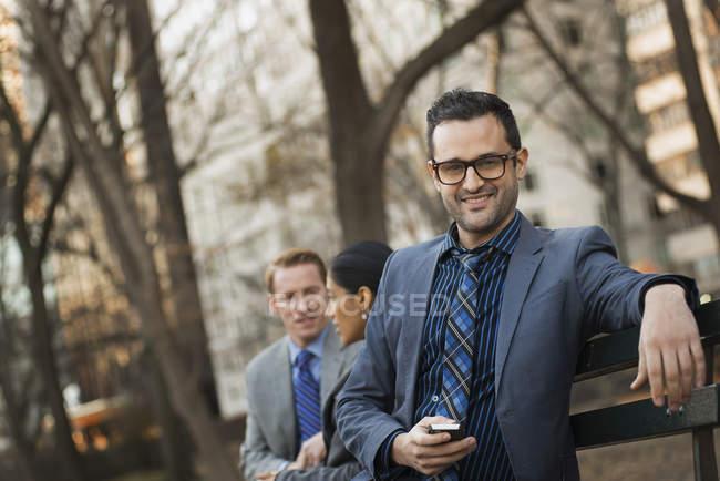 Uomo d'affari che tiene smartphone con colleghi che si rilassano sulla panchina nel parco cittadino . — Foto stock