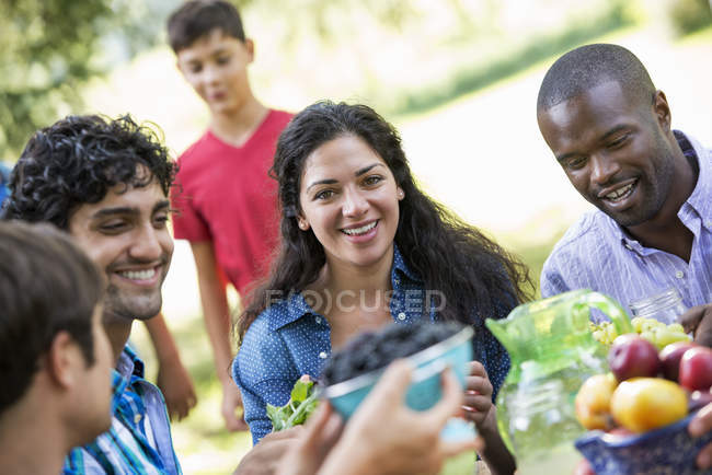 Adults and child around party table in country garden. — Stock Photo
