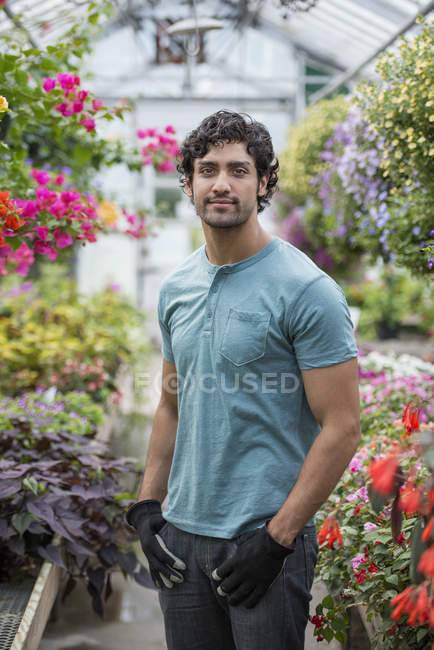 Young man standing in greenhouse full of flowering plants. — Stock Photo