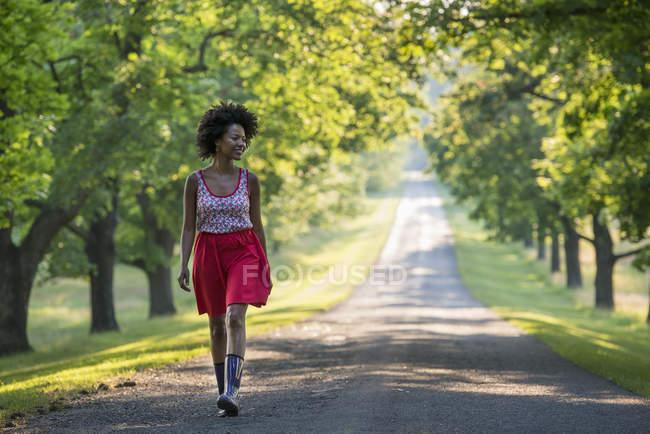 Donna che cammina sulla strada di campagna nel parco soleggiato . — Foto stock