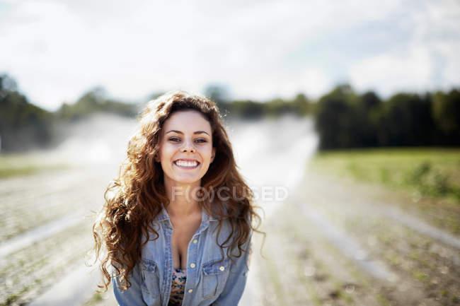 Jovem mulher de jaqueta de ganga em pé no campo com aspersores de irrigação . — Fotografia de Stock