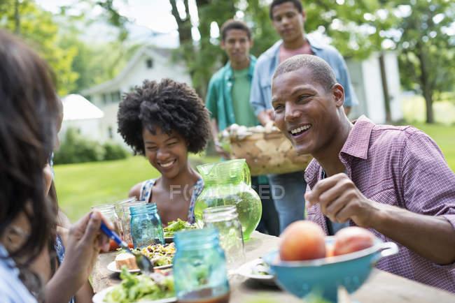 Jóvenes comiendo en el jardín del campo . — Stock Photo