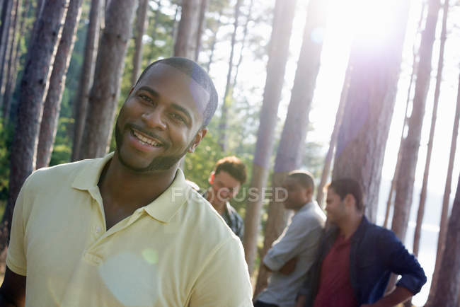 Mid adult man smiling and looking in camera with friends gathered in pine trees at lakeside. — Stock Photo
