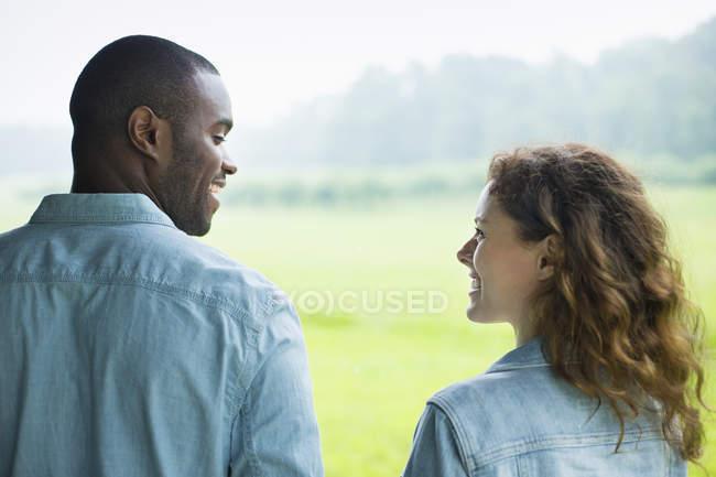 Junges paar nebeneinander im grünen Feld stehen und sahen einander. — Stockfoto