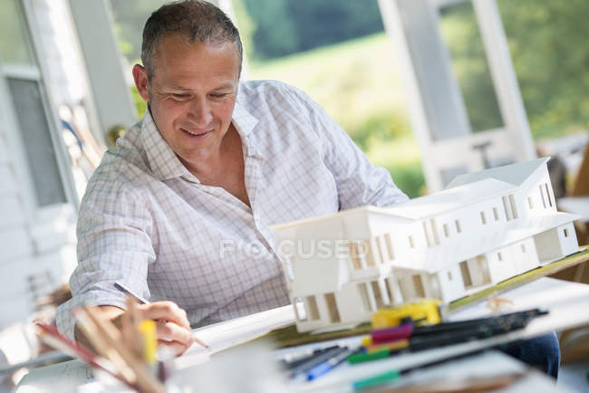 Mature man working on model of farmhouse at table in countryside. — Stock Photo