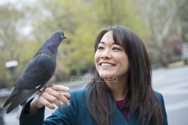 Young Asian woman holding perched pigeon on hand in city park. — Stock Photo