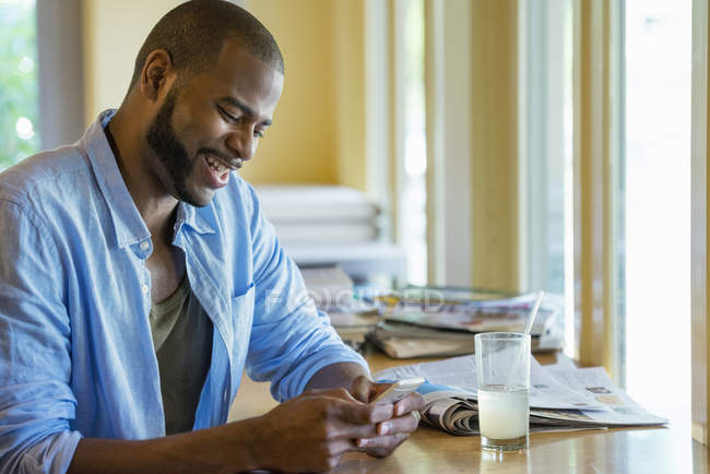 Man laughing and using smartphone at cafe table. — Stock Photo