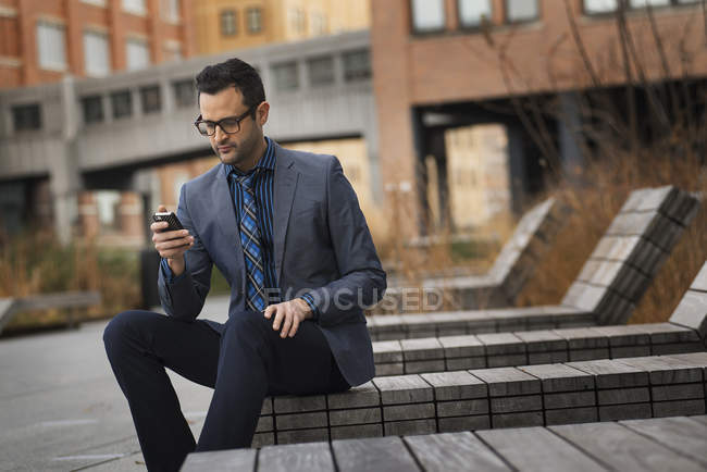 Man in formal wear sitting on bench and checking smartphone in city. — Stock Photo