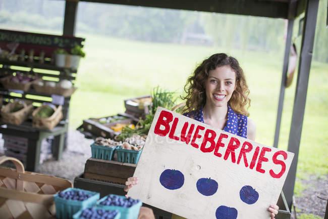 Donna che trasporta il segno di mirtilli in azienda agricola biologica — Foto stock