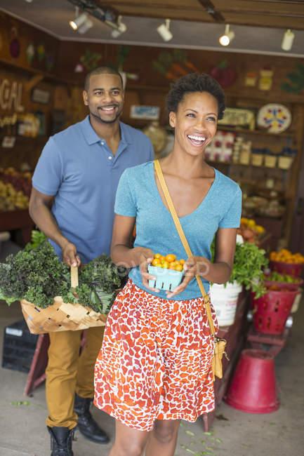 Man and woman choosing organic vegetables in farm shop. — Stock Photo
