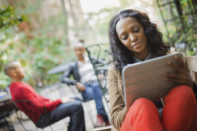 Woman using digital tablet in park with people talking in chairs in background. — Stock Photo