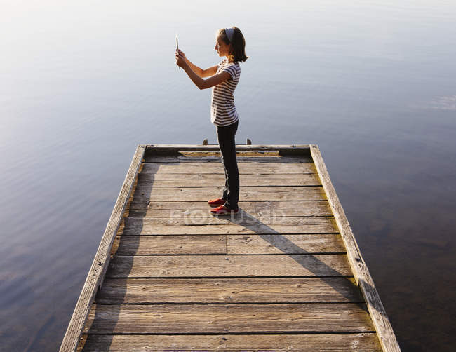 Pre-adolescent girl holding digital tablet while standing on wooden dock over water. — Stock Photo