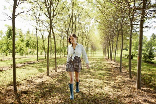 Mulher jovem caminhando na Avenida de árvores na floresta. — Fotografia de Stock