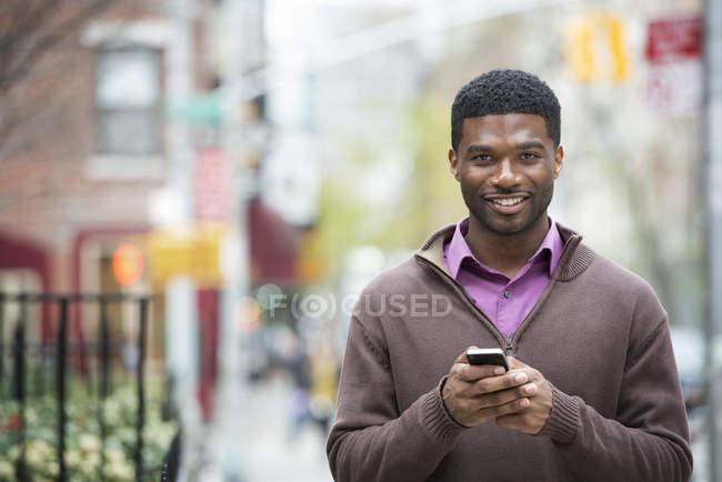 Jovem segurando telefone e sorrindo na câmera . — Fotografia de Stock