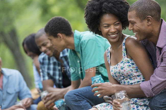 Cheerful young friends having drinks, talking and laughing in countryside garden. — Stock Photo