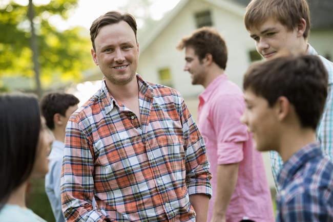 Grupo de adultos y adolescentes en la fiesta de verano en el país . - foto de stock