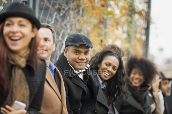 Grupo de personas en situación de ropa en línea en la calle - foto de stock