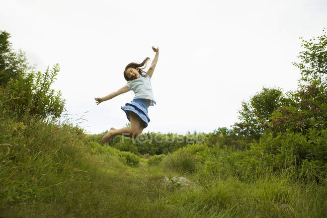 Pre-teen girl jumping in green meadow with arms outstretched. — Stock Photo