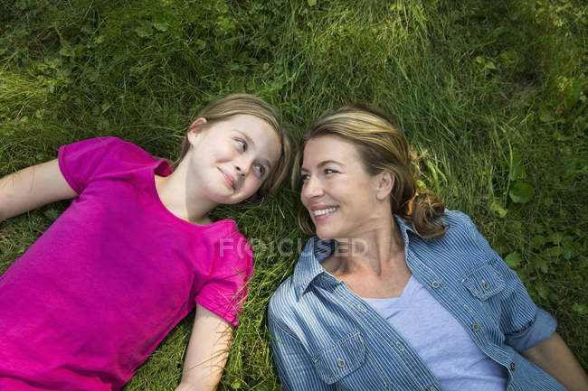 Mutter und Tochter am grünen Rasen liegen, schauen einander an und Lächeln. — Stockfoto