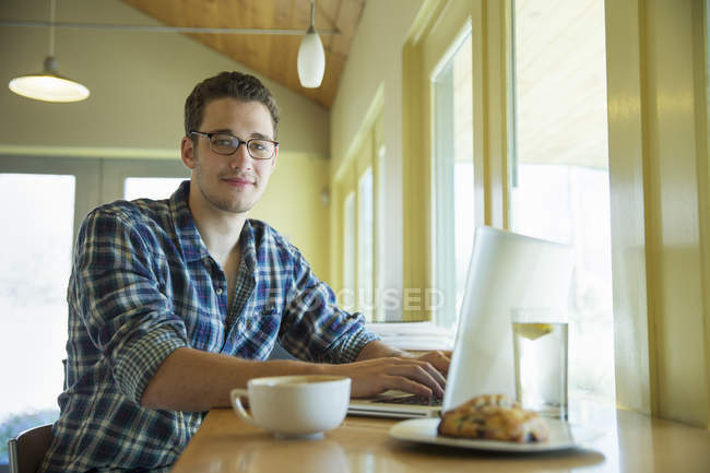 Young man sitting at cafe table with laptop and looking in camera. — Stock Photo
