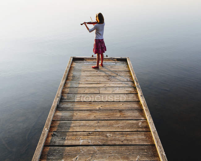 Pre-adolescent female violinist playing violin at dawn on wooden pier at lake. — Stock Photo