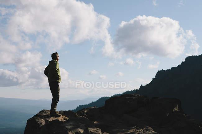 Escursionista maschio in piedi sulla scogliera rocciosa al crepuscolo — Foto stock