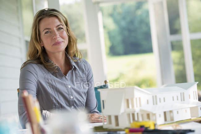 Середине взрослая женщина работает по модели фермерского дома за столом в сельской местности. — стоковое фото