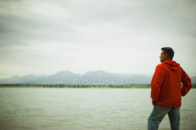 Homme mûr en veste rouge regardant la vue sur la campagne bord du lac . — Photo de stock
