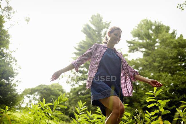 Woman walking through undergrowth in woodland with arms brushing wild plants. — Stock Photo
