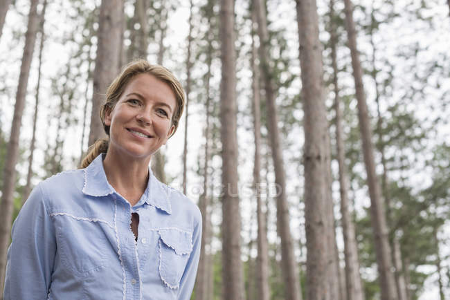 Низкий угол обзора женщины, стоящей среди деревьев в лесу . — стоковое фото