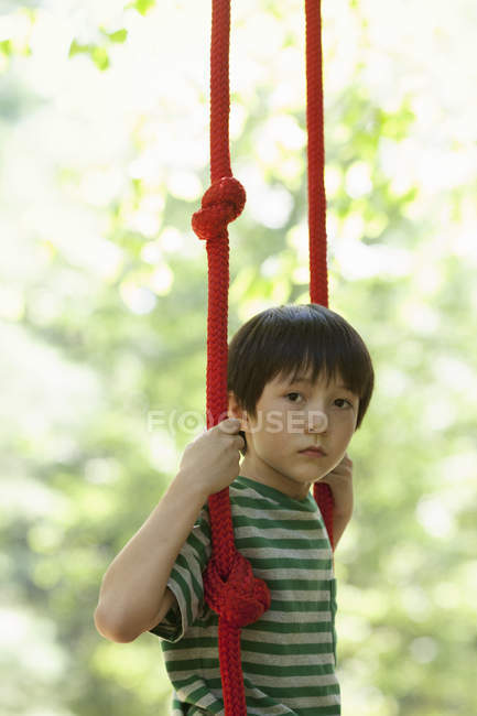 Elementary age boy sitting on swing outdoors. — Stock Photo