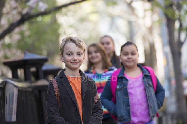 Blonder Junge und Gruppe vorpubertärer Kinder stehen auf Gehweg. — Stockfoto