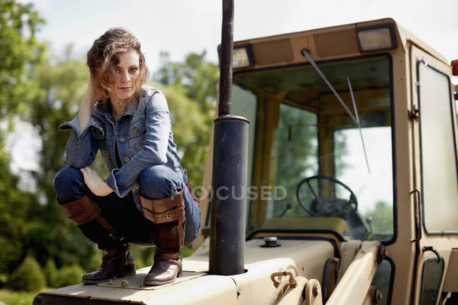 Young woman in denim jacket and boots crouching on hood of tractor. — Stock Photo