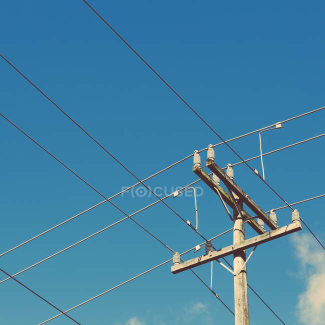 Telephone pole and power lines against blue sky. — Stock Photo